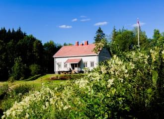 Bilde av hovedhuset sett fra innkjørselsen til gården